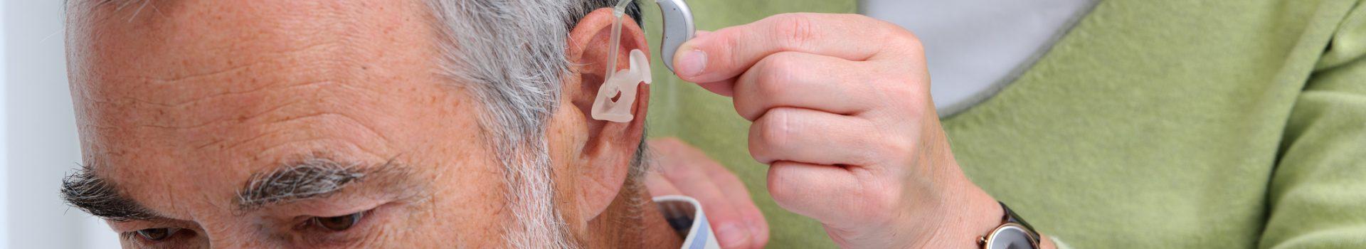 Dokter die hoortoestel in doet bij oudere man